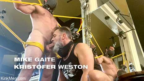 Mike Gaite stands naked, bound in bright yellow rope. A chain is attached to a leather collar around his neck which holds a metal hook, set deep in his ass. Kristofer Weston sits back stroking his cock through his shorts...