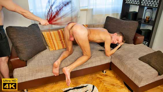 Stefan Mateo is gagged and shackled, with his legs in the air. That shows off his ass and the tight hole as his cock is hidden by his jockstrap. His tormentor runs a cane over the sexy ass and pulls on the nipple clamps too.